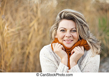 Happy middle aged woman with pullover and scarf