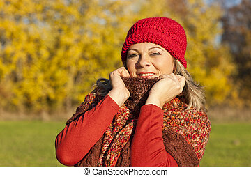 Happy middle aged woman with scarf and cap