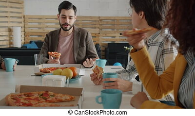 Happy Middle Eastern man is talking to Caucasian women colleagues eating pizza having fun at corporate party. Work breaks and youth concept.