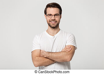 Happy millennial confident man in glasses standing with folded hands.
