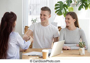 Happy millennial couple handshake broker meeting in office
