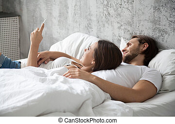 Happy millennial couple using mobile phone lying in bed together