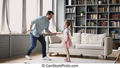 Full length happy millennial daddy inviting to dance small princess daughter at home. Smiling little preschool child girl holding father's hands, twisting to music together in modern living room.