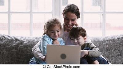 Happy millennial mom hug two kids teaching using laptop computer