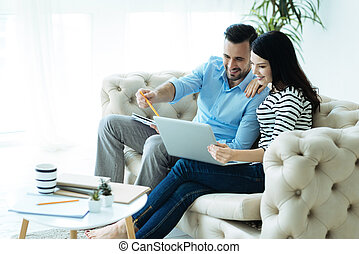 Happy millennial people focusing their attention on laptop