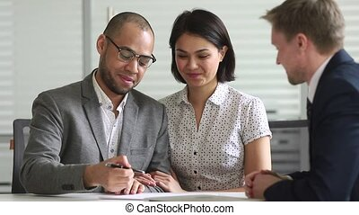 Happy mixed ethnicity couple signing bank loan contract handshake manager