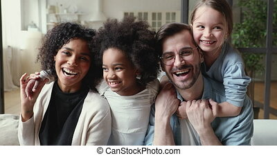 Happy mixed ethnicity family laughing, cuddling at home, portrait