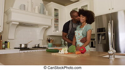 Happy mixed race couple cooking and dancing in their kitchen...