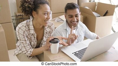 Happy mixed race couple discuss while using laptop