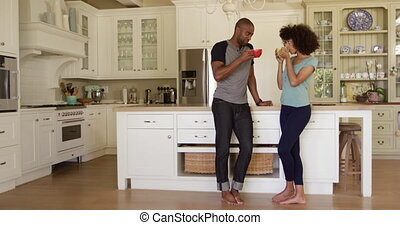 Happy mixed race couple drinking coffee in their kitchen