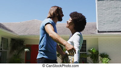 Happy mixed race couple hugging each other near new apartment house