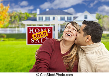 Mixed Race Couple in Front of Sold Real Estate Sign