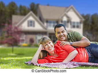 Happy Mixed Race Couple in Front of House