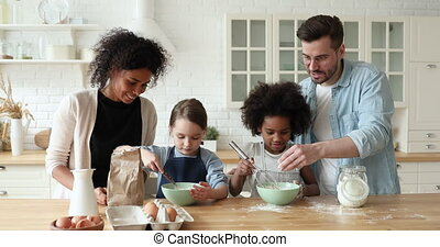 Happy mixed race cute kids helping young parents making ...