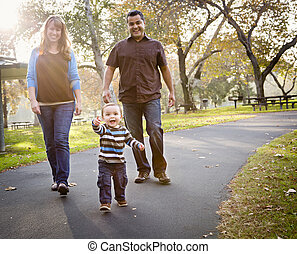 Happy Mixed Race Ethnic Family Walking In The Park