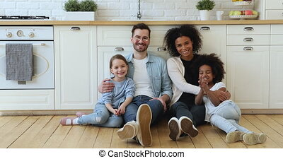 Happy mixed race family sitting on kitchen floor at home - ...