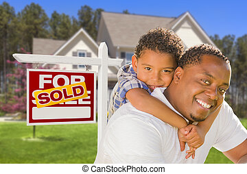 Happy Mixed Race Father and Son In Front of Sold Real Estate...