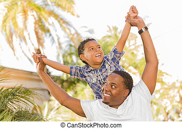 Mixed Race Father and Son Playing Piggyback