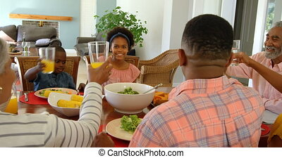 Happy mixed race multi-generation family toasting glasses of juice at dining table at home 4k