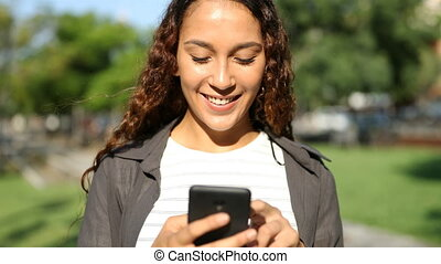 Happy mixed race woman using smart phone