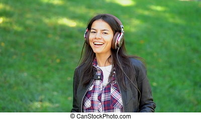 Happy mixed race young woman listening to music on...