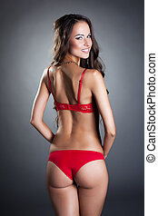 Happy model in red lingerie posing back to camera