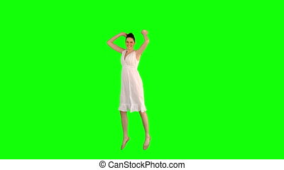 Happy model in white dress jumping on green background