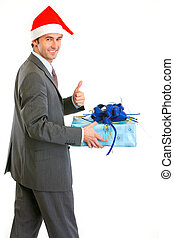 Happy modern businessman in Santa Hat holding present and showing thumbs up isolated on white