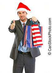Happy modern businessman in Santa Hat with shopping bags showing thumbs up isolated on white