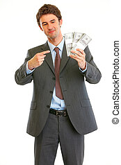 Happy modern businessman pointing on packs of dollars