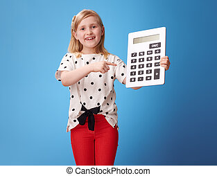happy modern child in red pants on blue pointing at calculator