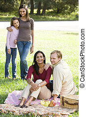 Happy modern multicultural family enjoying a picnic