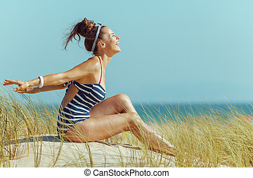 happy modern woman in striped swimwear on beach rejoicing