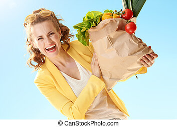 happy modern woman looking out from paper bag with groceries against blue sky