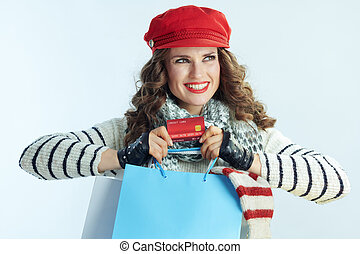 happy modern woman shopper with sweaters showing credit card