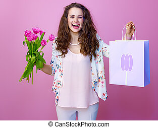 happy modern woman with bouquet of tulips showing shopping bag