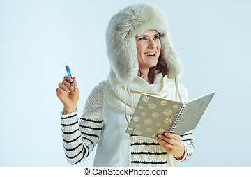 happy modern woman with notebook and pen looking at copy space