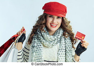 happy modern woman with shopping bags showing credit card