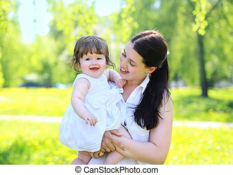 Happy mom and baby in the park in the summer, having fun, sunny