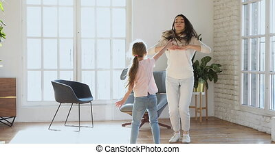 Happy mom and child daughter dancing jumping in living room