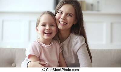 Happy mom and child daughter waving hands looking at camera