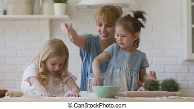 Happy family young mom and cute funny small children daughters laughing preparing sugaring dough for cookies together, smiling mother teaching kids siblings helping cooking baking pastry in kitchen