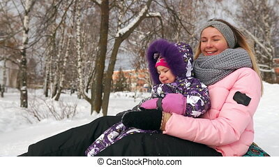 Happy mom and daughter sledding in winter in snow and...