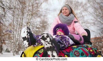 Happy mom and daughter sledding in winter in snow and playing snowballs. mother and child laugh and rejoice glide on an inflatable tube. Family playing park during Christmas holidays. Slow motion