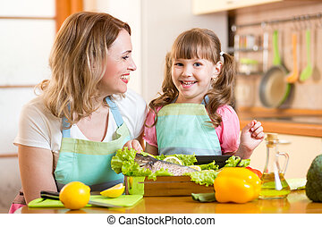 happy mom and kid cooking healthy food in kitchen