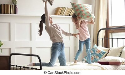 Happy mom and kid daughter enjoy pillow fight on bed