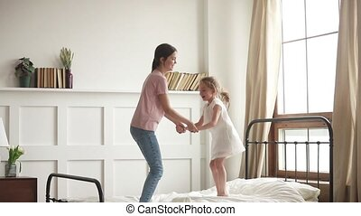 Happy mom and kid daughter holding hands jumping on bed