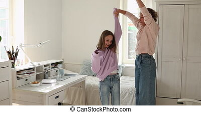 Happy mom and teen daughter dancing jumping at home