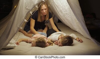 Happy mom enjoys family vacation with her children son and daughter in a tent in the living room, massages the children