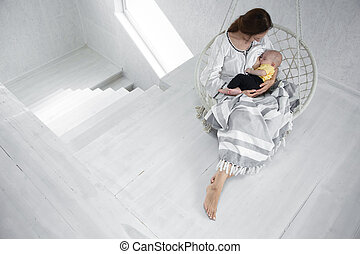 Happy mom feeds a baby in a white hammock with a blanket on the background of a white room. Happy motherhood concept.